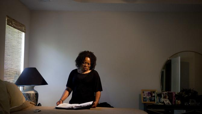 Patricia Jackson sifts through bank documents in the bedroom of her home Saturday, June 16, 2012, in Marietta, Ga. On a suburban cul-de-sac northwest of Atlanta, the Jacksons are struggling to keep a house worth $100,000 less than they owe. Their voices and those of many others tell the story of a country that, for all the economic turmoil of the past few years, continues to believe things will get better. But until it does, families are trying to hang on to what they've got left. The Great Recession claimed nearly 40 percent of Americans' wealth, the Federal Reserve reported last week. The new figures, showing Americans' net worth has plunged back to what it was in 1992, left economists shuddering. (AP Photo/David Goldman)