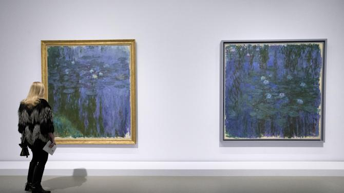 "A visitor looks at ""Blue Water Lilies, and Water Lilies, 1916-1919 of Claude Monet as part of the opening of the exhibition ""Keys to a Passion"" at the Louis Vuitton Foundation in Paris, France, Monday, March 30, 2015. The exhibition, third stage of the inauguration of Louis Vuitton Foundation, which runs from April 1 to July 6, 2015. (AP Photo/Francois Mori)"