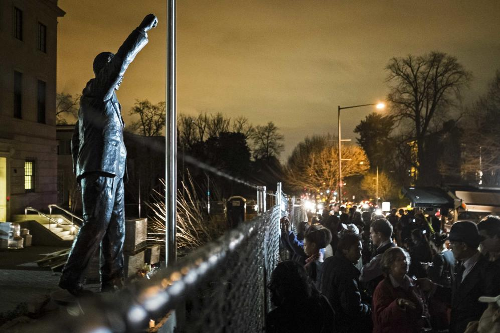 Crowd gathers outside the South Africa embassy near a statue of Nelson Mandela, after his passing, in Washington