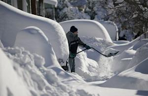 A resident shovels snow away from the entrance to his …