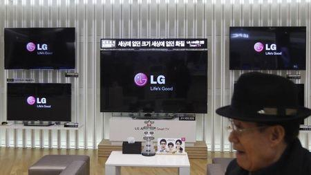 A customer walks in front of LG TV sets which are made with LG Display flat screens, at a store in Seoul