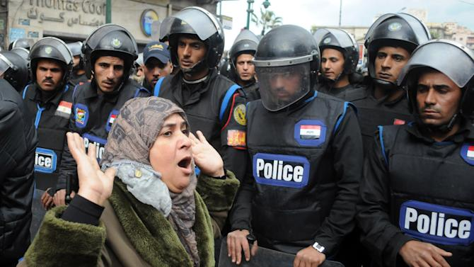 A woman reacts as she stands before riot policemen separating opponents of Egyptian President Mohammed Morsi clashing with Islamist supporters of the president in Alexandria, Egypt, Friday, Dec. 21, 2012. Thousands of Islamists clashed with their opponents Friday in Egypt's second largest city, Alexandria, on the eve of the second leg of voting on the country's contentious constitution that has deeply polarized the nation.(AP Photo)