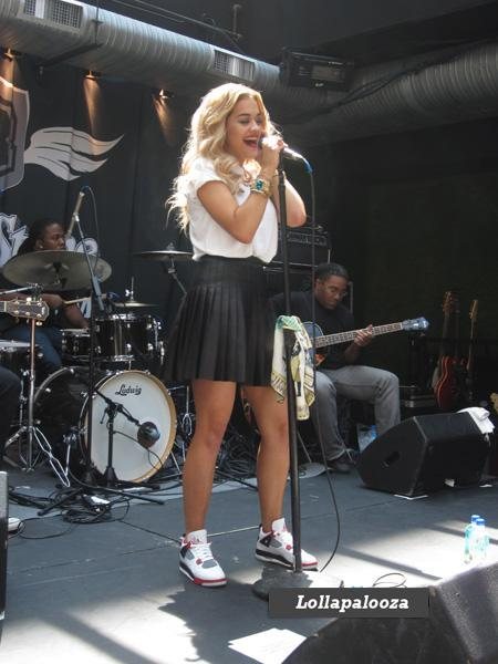 Rita Ora is a vision in blonde ringlets, a classic white tee, pleated black leather mini skirt and pristine Jordans at her performance.