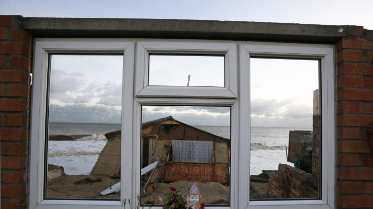 A garden gnome sits on the window of a house that fell into the sea during a storm surge in Hemsby, eastern England