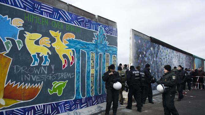 German police officers protect a part of the former Berlin Wall in Berlin, Germany, Friday, March 1, 2013. Construction crews stopped work Friday on removing a small section from one of the few remaining stretches of the Berlin Wall to make way for a condo project after hundreds of protesters blocked their path. (AP Photo/Markus Schreiber)