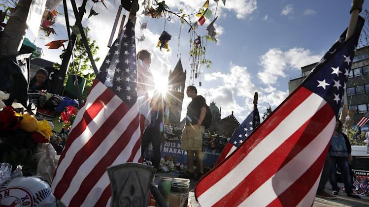 People walk through a makeshift memorial near the Boston Marathon finish line in Boston's Copley Square Tuesday, May 7, 2013, in remembrance of the Boston Marathon bombings. (AP Photo/Steven Senne)