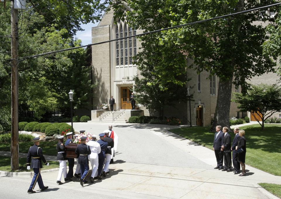 Members of the Ford family, Jack Ford, Mike Ford, Steve Ford and Susan Ford Bales, watch as the casket bearing the body of former first lady Betty Ford is carried by members of the armed forces into Grace Episcopal Church in Grand Rapids, Mich., Thursday, July 14, 2011. (AP Photo/Carlos Osorio)