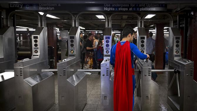 A man in a Superman costume enters the subway at the conclusion of day two of New York Comic Con in Manhattan, New York