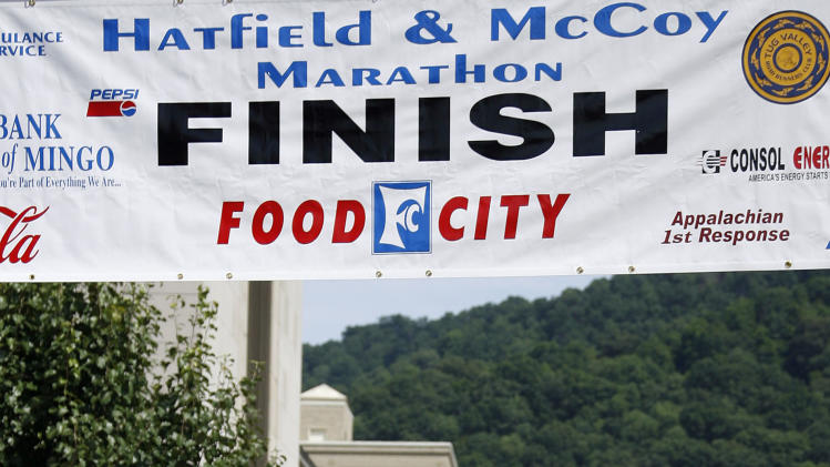 In a Saturday, June 9, 2012 photo, Doyle Van Meter, left, dressed as Randall McCoy and Jerry Akers, right, as Devil Anse Hatfield congratulate Laura Yevchak of Indiana, Pa., as she finishes the Hatfield-McCoy Marathon in Williamson, W.V. (AP Photo/ James Crisp)