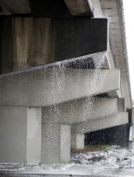 Runoff water from melting snow makes a waterfall from an overpass along I-55 in Jackson, Miss., Thursday, Jan. 17, 2013. A winter storm system left 2 to 4 inches of snow in parts of central Mississippi before heading east toward Alabama, the National Weather Service said. (AP Photo/Rogelio V. Solis)