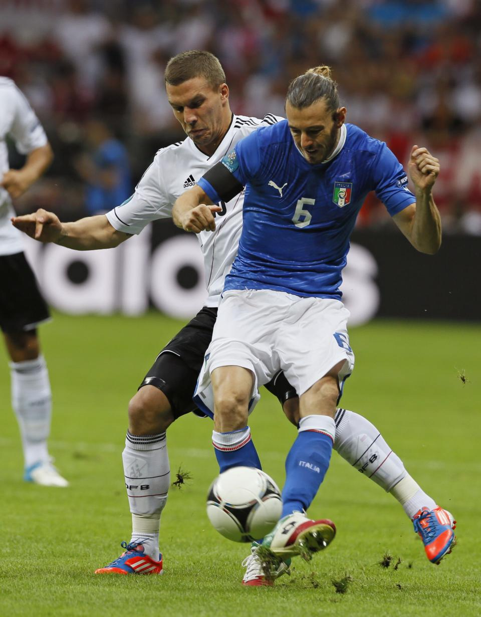 Germany's Lukas Podolski, left,  challenges Italy's Federico Balzaretti during the Euro 2012 soccer championship semifinal match between Germany and Italy in Warsaw, Poland, Thursday, June 28, 2012. (AP Photo/Frank Augstein)