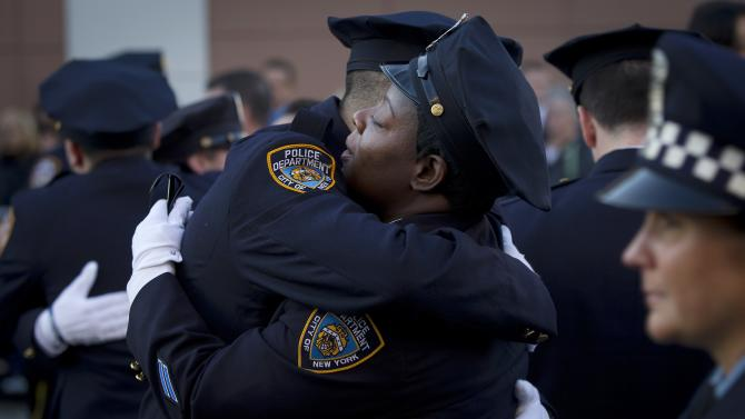 Police officers hug before NYPD officer Rafael Ramos' funeral at Christ Tabernacle Church to it's final resting place in the Queens borough of New York