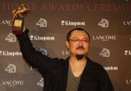 "Director Wuershan of Mongolia shows his award for the Best New Director category at the 48th Golden Horse Awards in Hsinchu, north eastern Taiwan. Wuershan won for his film ""The Butcher, the Chef, and the swordsman. (AP Photo/Wally Santana)"