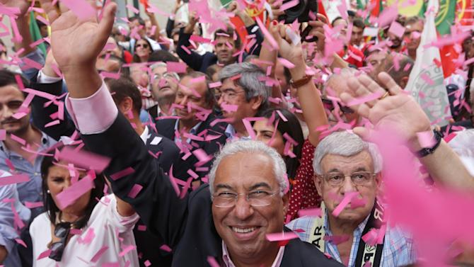 Antonio Costa, leader of the Portuguese Socialist Party, waves while being showered with confetti during an election campaign march through downtown Lisbon, Friday, Oct. 2 2015. Portugal goes to the polls to elect a new government on Sunday. (AP Photo/Armando Franca)