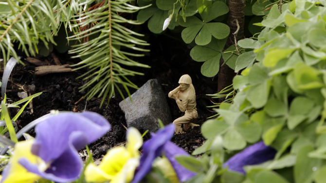 A tiny bazooka-wielding army figure crouches behind a rock deep in the flowers and foliage of Mill Ends Park in Portland, Ore., Thursday, April 11, 2013.  Tiny battle lines are being drawn in a whimsical British-American dispute over which country has the world's smallest park. Two feet in diameter, Portland's Mill Ends Park holds the title of world's smallest park in the Guinness Book of World Records. But a rival has emerged--Prince's Park, more than 5,000 miles away in the English town of Burntwood  which holds the record for smallest park in the United Kingdom.(AP Photo/Don Ryan)