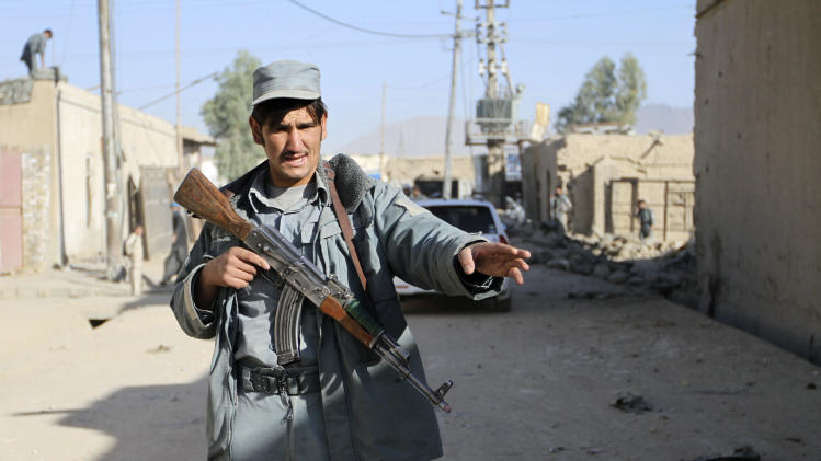 An Afghan policeman stops media members from entering at the scene of a suicide attack in Kandahar, south of Kabul, Afghanistan, Thursday, Nov. 8, 2012. Ahmad Jawed Faisal, a provincial governor spokesman, says a suicide bomber killed several policemen and wounded others in the southern city of Kandahar on Thursday. (AP Photo/Allauddin Khan)