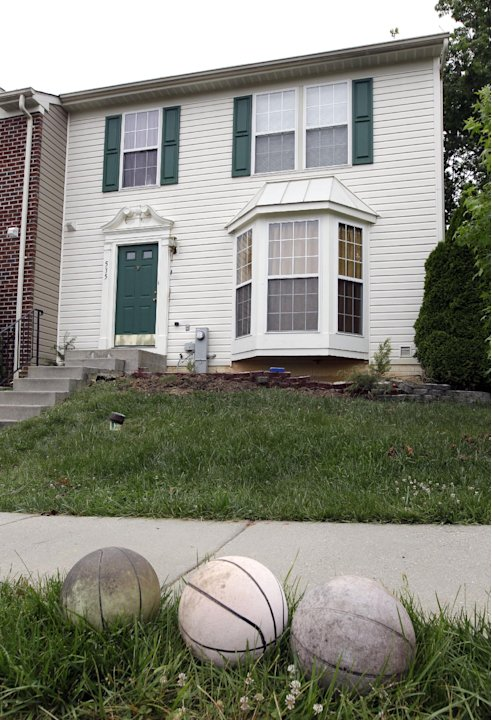 Old basketballs sit on the curb outside of a house in Joppatowne, Md., Friday, June 1, 2012, where a 21-year-old college student accused of killing a housemate told police he ate the victim's heart an