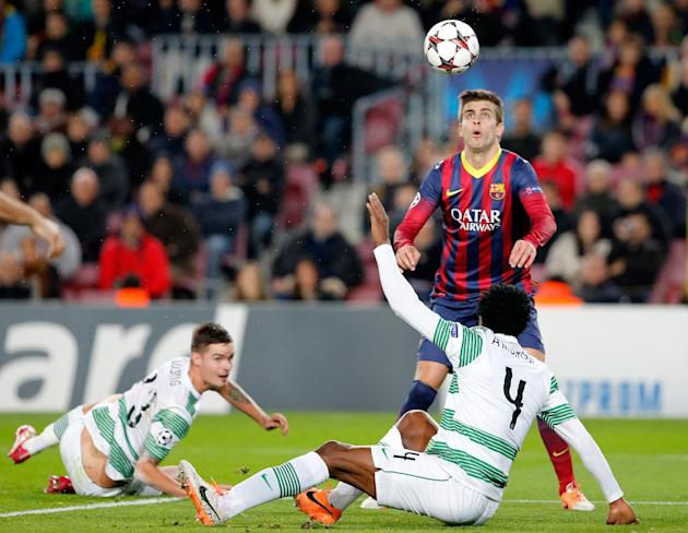 Barcelona's Gerard Pique, background right, eyes the ball during a Group H Champions League soccer match between FC Barcelona and Celtic FC at the Camp Nou stadium in Barcelona, Spain, Wednesday D