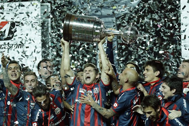 Walter Kannemann of Argentina's San Lorenzo, center, lifts the trophy after winning the 2014 Copa Libertadores championship against Paraguay's Naciona...