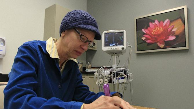 Kathleen Sanford performs neurological cognitive tests during an appointment Monday, Dec. 17, 2012, in Columbus, Ohio. Sanford is an Alzheimer's patient that has a deep brain stimulation implant as part of a study at Ohio State University. In small experiments, scientists are implanting pacemaker-like devices deep in the brains of some people with early-stage Alzheimer's in hopes of slowing the disease's damage. The tiny wires send mild jolts of electricity to stimulate the brain.  (AP Photo/Jay LaPrete)