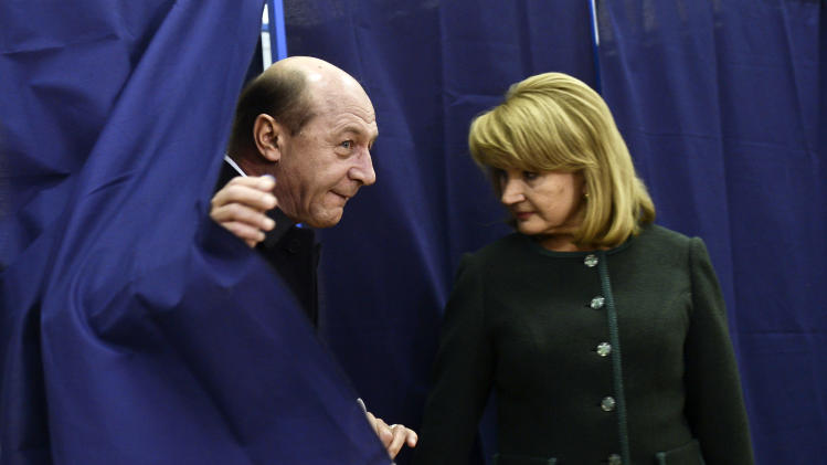 Romania's President Traian Basescu, left, exits a voting cabin as his wife Maria, right, stands by, in Bucharest, Romania, Sunday, Dec. 9, 2012. Millions of Romanians braved rain and snow Sunday as they went to the polls for a parliamentary election that center-left government is expected to win a, but the result could lead to more of the political instability that has plagued the impoverished Balkan nation this year. (AP Photo)