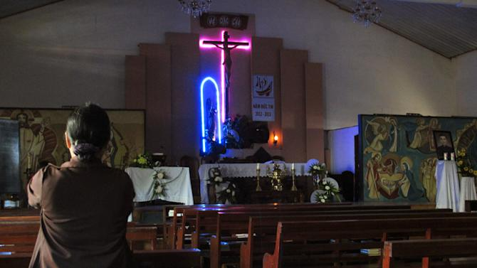 In this Tuesday, Sept. 24, 2013 photo, a worshipper prays in a church ahead of an afternoon mass in the Vietnamese central highland town of Pleiku. Communist Vietnam allows state-sanctioned faiths to grow, but continues to keep a close watch on all religious institutions. (AP Photo/Chris Brummitt)