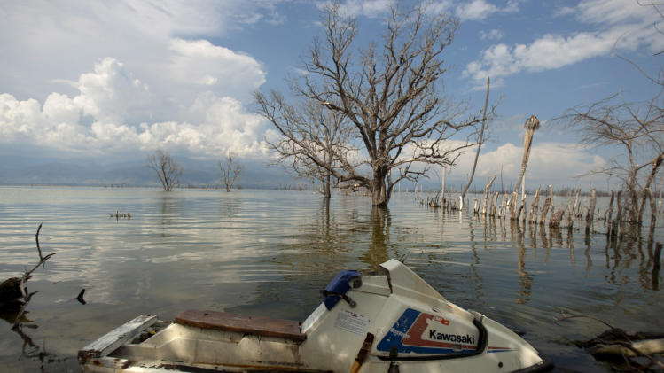 In this Sept. 5, 2012 photo, a jet ski sits parked on the shores of Lake Enriquillo in Jimani, Dominican Republic, near the border with Haiti. The waters' rise has worsened exponentially in recent years, especially after heavy rains in 2007 and 2008 hit the island of Hispaniola. Tropical Storm Isaac dumped more water on the region last month, sparking more damage. (AP Photo/Dieu Nalio Chery)