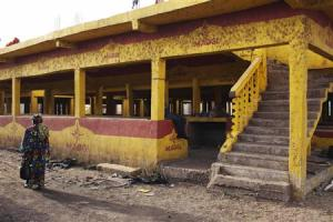 Woman walks past an abandoned marketplace in Bamako