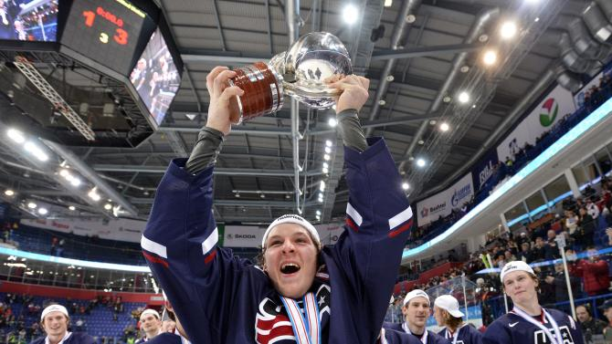Team USA captain Jake McCabe, centre, hoist the World Junior Trophy after his team defeated Sweden during third period gold medal hockey action at the IIHF World Junior Championships in Ufa, Russia, on Saturday, Jan. 5, 2013. (AP Photo/The Canadian Press, Nathan Denette)
