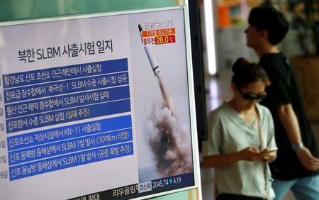 Passengers walk past a TV screen broadcasting a news report on North Korea's submarine-launched ballistic missile fired from North Korea's east coast port of Sinpo, at a railway station in Seoul