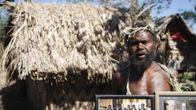 In this Sunday, May 31, 2015 photo, Albi Nagia poses with photographs of Prince Philip in Yakel, Tanna island, Vanuatu. Nagia is part of a movement which worships the prince as the son of their ancestral God. (AP Photo/Nick Perry)