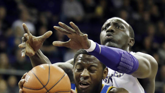 UCLA's Jordan Adams (3) grabs a rebound in front of Washington's Aziz N'Diaye during the first half of an NCAA college basketball game, Saturday, March 9, 2013, in Seattle. (AP Photo/Ted S. Warren)