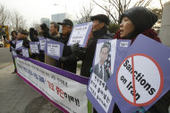 "South Korea protesters shout slogans during a rally opposing a visit of Robert Einhorn, U.S. State Department's special adviser for nonproliferation and arms control, in front of the foreign ministry in Seoul, South Korea, Tuesday, Jan. 17, 2012. Einhorn is urging South Korea to reduce its crude oil imports from Iran to put pressure on Tehran over its nuclear program. The letters on the banner read: ""Stop sanctions on Iran."" (AP Photo/Ahn Young-joon)"