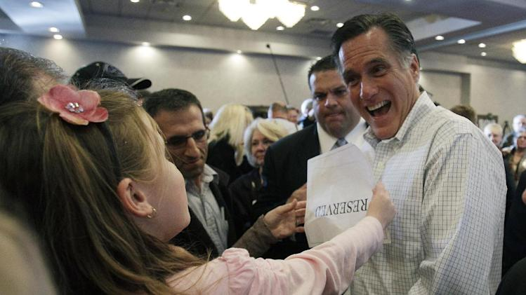 Republican presidential candidate, former Massachusetts Gov. Mitt Romney, autographs a baseball as he greets the crowd after a Tea Party town hall event in Milford, Mich., Thursday, Feb. 23, 2012. (AP Photo/Carlos Osorio)