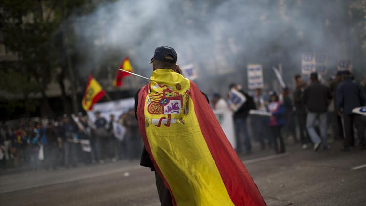 A police officer wearing a Spanish flag walks in front of a demonstration where other police officers protest by blocking the street in front of the Interior Ministry in Madrid, Spain, Saturday, Oct. 27, 2012. The demonstrators were protesting the government's austerity measures, especially the elimination of their Christmas bonus pay, one of 14 paychecks that most Spanish civil servants get each year. (AP Photo/Emilio Morenatti)