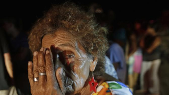 A resident looks on as she waits for food aid and water distributed by the federal police in Cabo San Lucas