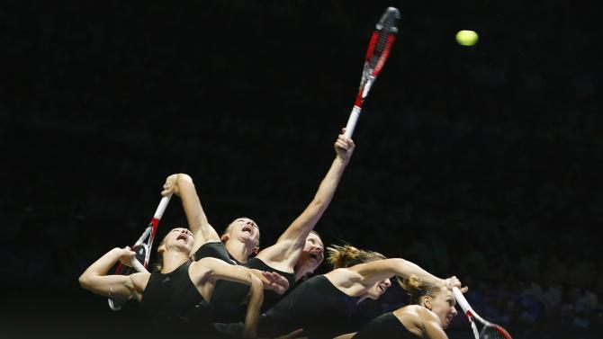 Simona Halep of Romania serves against Agnieszka Radwanska of Poland during their WTA Finals singles semi-final tennis match at the Singapore Indoor Stadium