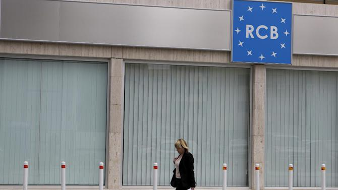A woman passes outside of the a Russian commercial bank in capital Nicosia, Cyprus, Tuesday, March 19, 2013.  A high proportion of deposits in Cypriot banks are believed to be held by Russians and Cypriot Finance Minister Michalis Sarris is flying to Moscow Tuesday to meet with his Russian counterpart.  Financial markets are reported to be tense Tuesday as investors await a vote in Cyprus on a contentious plan to help fund the country's bailout by a one off charge on bank deposits although there may be a change to the proposed levy to spare small account holders. (AP Photo/Petros Karadjias)