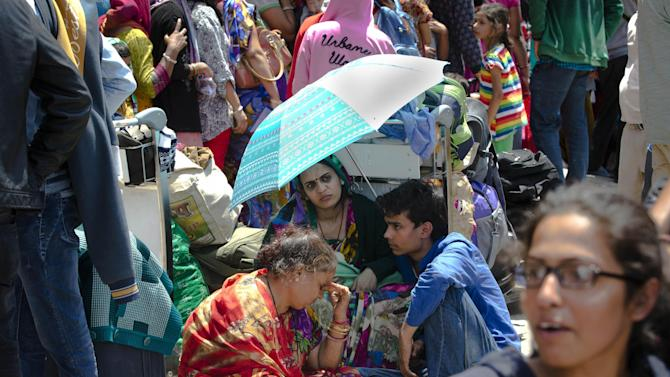 Indian tourists wait in a queue to be evacuated by special Indian Air Force plane at the Nepal International airport in Kathmandu, Nepal, Monday, April 27, 2015. A strong magnitude earthquake shook Nepal's capital and the densely populated Kathmandu valley on Saturday devastating the region and leaving tens of thousands shell-shocked and sleeping in streets. (AP Photo/Manish Swarup)