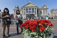 Two Japanese tourists look at a city map in front of the Concertgebouw music theater on the Museum square in Amsterdam April 24, 2013. REUTERS/Michael Kooren