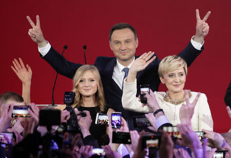 Duda, presidential candidate of the Law and Justice Party (PiS), his wife Agata and daughter Kinga flash Victory signs after the results of the exit polls on the second round of presidential elections in Warsaw