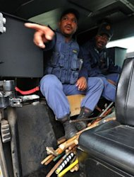 Police carry arms confiscated from miners in Marikana. South African police fired rubber bullets, raided worker hostels and seized traditional weapons at platinum giant Lonmin in a crackdown on rising unrest in the key mining industry