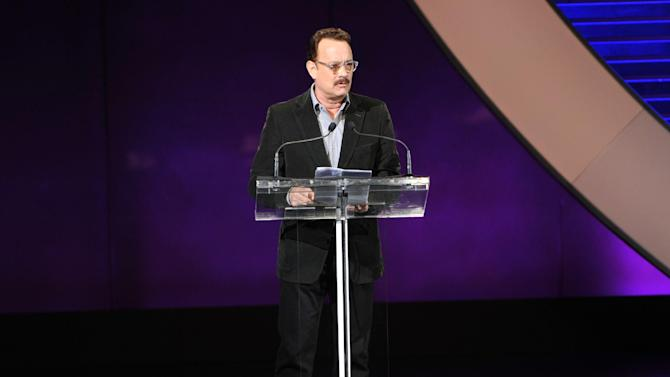 """This image released by Women in the World Conference shows actor Tom Hanks offering a special tribute to the late writer-director Nora Ephron at the Women in the World Conference, Friday, April 5, 2013, in New York. Hanks starred in Ephron's films """"Sleepless in Seattle,"""" and """"You've Got Mail,"""" and is currently performing on Broadway in Ephron's """"Lucky Guy.""""  Ephron died June 26, 2012, of leukemia at the age of 71. (AP Photo/Women in the World Conference, Marc Bryan-Brown)"""