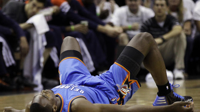 Oklahoma City Thunder power forward Serge Ibaka (9), from the Republic of Congo, stays on the floor after being called for fouling San Antonio Spurs shooting guard Manu Ginobili during the first half of Game 5 in the NBA basketball Western Conference finals, Monday, June 4, 2012, in San Antonio. (AP Photo/Eric Gay)