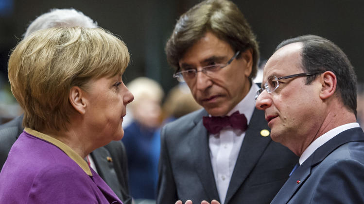 German Chancellor Angela Merkel, left, speaks with French President Francois Hollande, right, during a round table meeting at an EU summit in Brussels on Friday, March 15, 2013. On the second anniversary of an uprising that evolved into Syria's brutal civil war, the European Union's national leaders will likely discuss whether to arm rebels trying to overthrow the regime of Bashar Assad. (AP Photo/Geert Vanden Wijngaert)