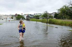 Vacationer Cornwell of Tennessee carries her eight-month-old son Riley, through a flooded street after Hurricane Arthur passed through in Manteo