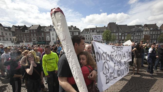"""A demonstrator carrying a larger-than-life mock marijuana joint attends a protest rally against the new marijuana buying policy in Maastricht, southern Netherlands, Tuesday May 1, 2012. A policy barring foreign tourists from buying marijuana in the Netherlands goes into effect in parts of the country Tuesday, with a protest planned in the southern city of Maastricht. Weed is technically illegal in the Netherlands, but it is sold openly in small amounts in designated cafes under the country's famed tolerance policy. The government has said that as of May 1, only holders of a """"weed pass"""" will be allowed to purchase the drug, and nonresidents aren't eligible. (AP Photo/Peter Dejong)"""