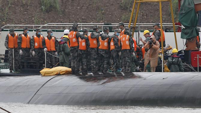 Rescue workers taking their pictures atop a sunken ship are seen during a media trip to the site of the sinking, organized by the Chinese goverment, in the Jianli section of Yangtze River, Hubei province