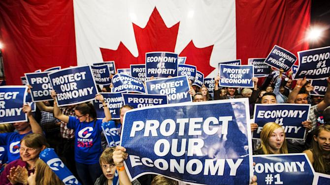 Supporters hold signs at Canada's PM and Conservative leader Harper's capmaign rally in London