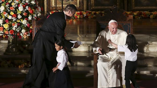 Pope Francis is greeted by children as he meets members of the civil society at the San Francisco Church in Quito